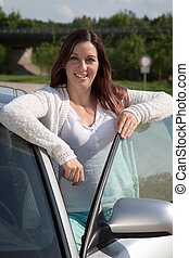 Young woman leaning at the car door