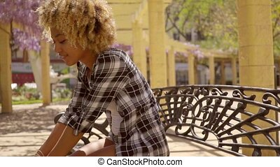 Young Woman Leaning Forward on Metal Bench - Side Profile...