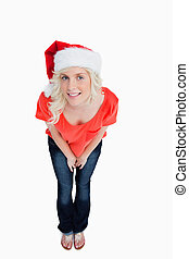 Young woman leaning her body forward and wearing the Santa Claus hat