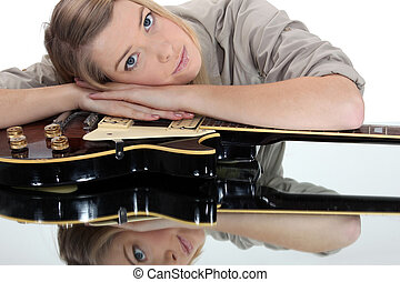 Young woman leaning on a guitar