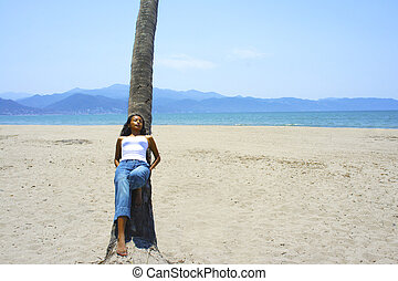 Young woman leaning on a palm tree