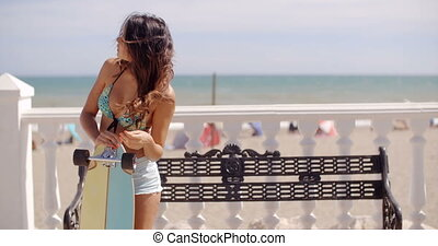 Young woman leaning on her skateboard as she bends forwards...