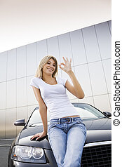 new car - Young woman leaning on new car and similing