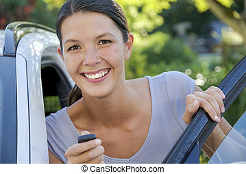 young woman leans against her car
