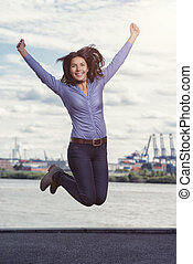 Young woman leaping and cheering for joy