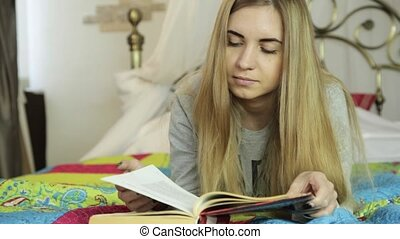 young woman learning at home. girl reading a book on a bed