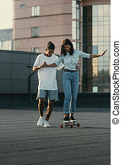 young woman learning to ride skateboard