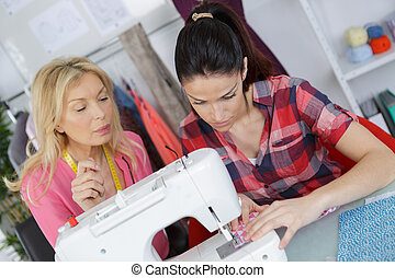young woman learning to use a sewing machine