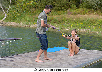 young woman learning to wakeboarding