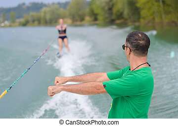 young woman learning water ski with coach