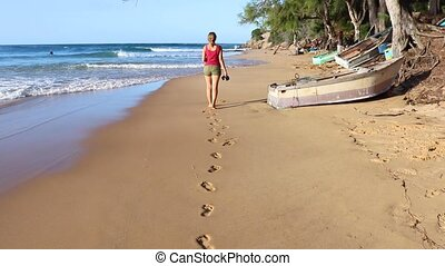 Young Woman Leaving Footprints on Sandy Beach