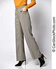 Young woman legs walking in new gray classic pants in the box from suit on a white