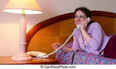 Young woman lies on bed and talks phone in room with lamp