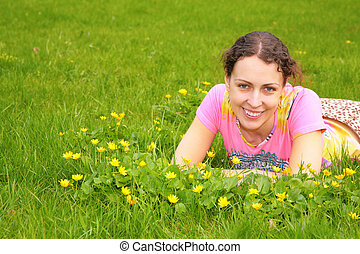 young woman lies on grass