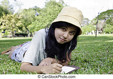 Young woman lies on green summer meadow with book