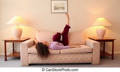 Young woman lies on sofa and shake legs at room with lamps on each side