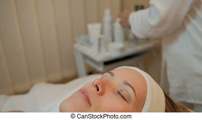 Young woman lies with closed eyes in cosmetology clinic...