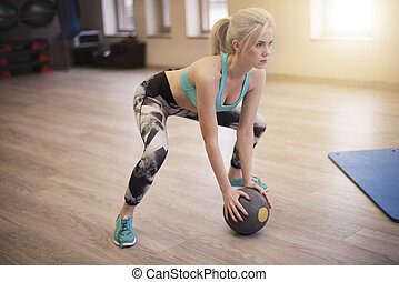 Young woman lifting a medicine ball