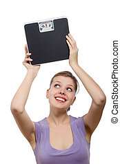 woman lifting a weight scale over her head