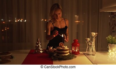 Young woman lighting a Sparkler in the cake at night at Christmas time