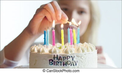 Young woman lighting candles on happy birthday cake