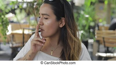 Young woman lighting up a cigarette outdoors cupping the...