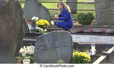 Young woman lights candle lantern in memory of husband father in cemetery. 4K
