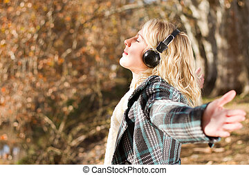 listening music - young woman listening music in autumn...