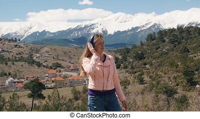 Young woman listening music with headphones outdoors