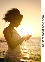 Young woman listening to music at sunset - Young woman ...