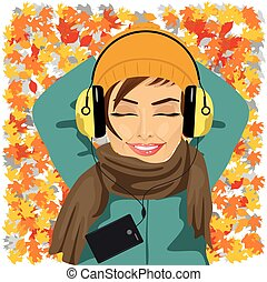 young woman listening to music lying on autumn leaves floor