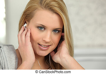 Young woman listening to music on earphones