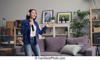 Young woman listening to music singing dancing in home jumping on sofa