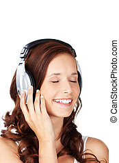 Young woman listening to music wearing a set of earphones...
