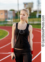 young woman listening to music while doing sport