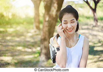 Young woman listening to music with earphones on smart phone app in park