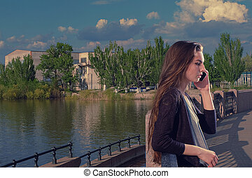 Young woman listening to the conversation using her mobile phone with a serious expression on her face, she standing outdoors on granite embankment against a river backdrop, toned image, copyspace.
