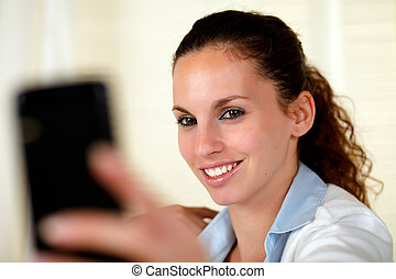 Young woman looking and smiling to cellphone