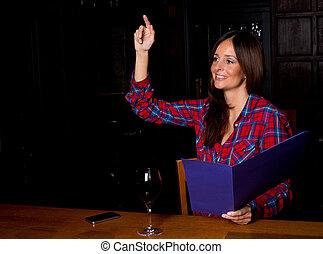 young woman looking at a menu.