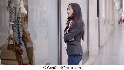 Young woman looking at a shop mannequin through a store...