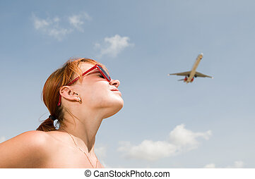 Young Woman looking at an airplane
