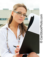 Young woman looking at documents outdoors