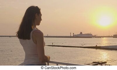 Young woman looking at evening sunset in sea. Evening sky landscape