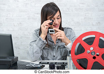young woman looking at film slide with magnifying glass