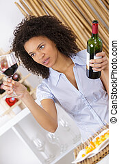 young woman looking at glass of red wine