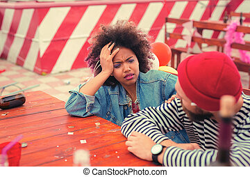 Young woman looking at her boyfriend and having headache after party
