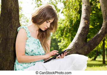 Young woman looking at her tablet