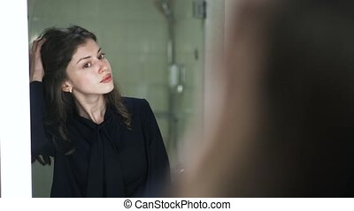 Young woman looking at herself in a mirror