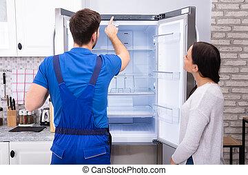 Serviceman Checking Temperature Of Refrigerator