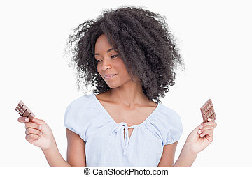 Young woman looking at one of her two pieces of chocolate